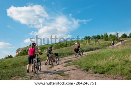 A group of tourists on a mountain bike ride on dirt roadagainst a beautiful sky. - stock photo