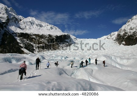 A group of tourists take a guided walk on Fox Glacier South Island New Zealand - stock photo