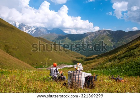 A group of tourists with big backpacks relaxes on a green meadow with mountain views - stock photo