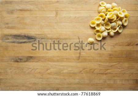 A group of uncooked orecchiette sits in the corner of a worn cutting board - stock photo