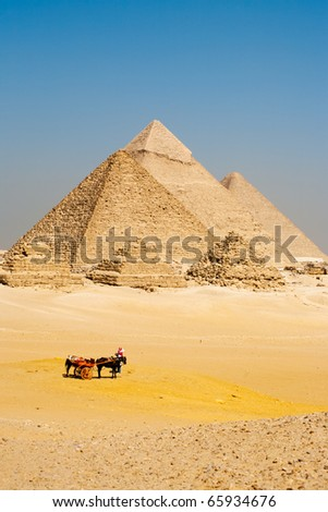 A group of unrecognizable Egyptian tourists dismount their horse cart to view all the pyramids of Giza in a line. - stock photo