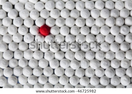 a group of usual white swabs with one unusual red - stock photo
