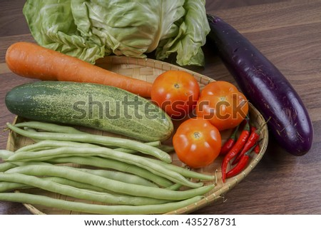 A group of vegetables in a basket.  Cabbage, cucumber,tomato, carrot and beans. Selective focus