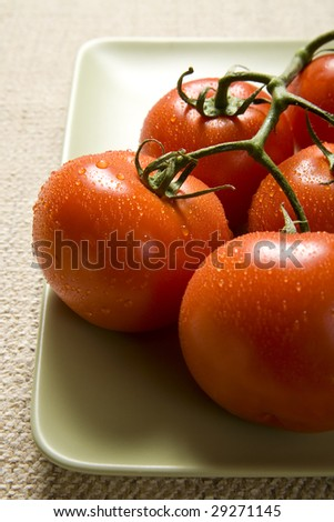 A group of vine ripe tomatoes glisten on a green plate. - stock photo