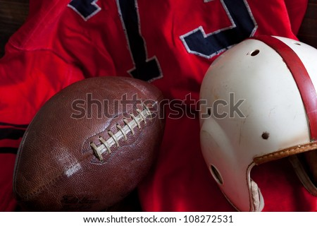 A group of vintage, antique American football equipment including a jersey, football and a helmet