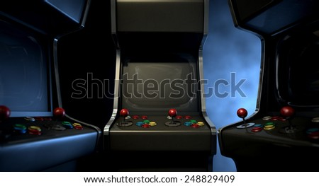 A group of vintage unbranded arcade games with a joysticks and buttons and a blank screen huddled facing each other on a dark ominous background with copy space - stock photo