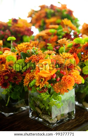 a group of wedding centerpieces in glass jars. orange and green colors - stock photo