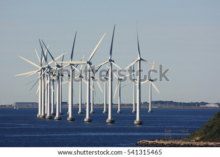 A group of wind turbines in the Sea off the coast of Denmark.