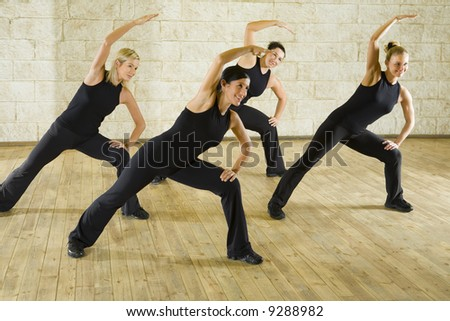 A group of women exercising in the fitness club. They're smiling. Front view. - stock photo