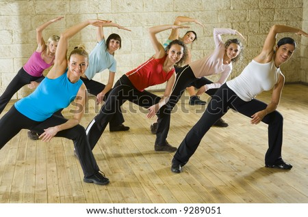 A group of women working out in the fitness club making stretching exercise. They're smiling and looking at camera. Front view. - stock photo