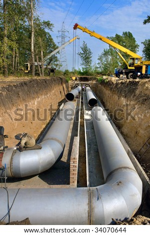 A group of workers are constructing a trunk pipeline in the ditch. - stock photo