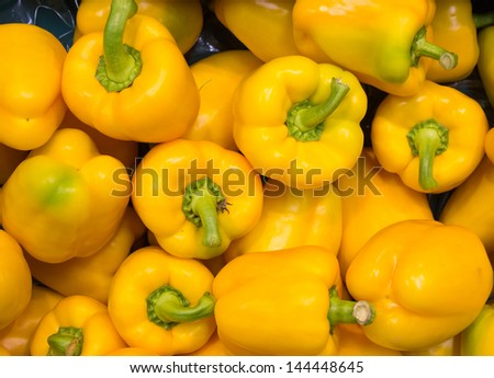A group of yellow peppers, displayed at the supermarket. - stock photo