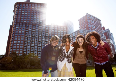 A group of young adults in a city park - shot into the sun with solar flare - stock photo
