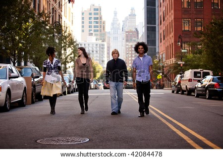 A group of young adults in an uban setting - walking on a road - stock photo