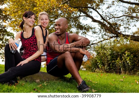 A group of young adults resting after exercise in the park - stock photo