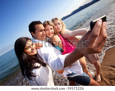 A group of young adults taking a self portrait with a cell phone - stock photo