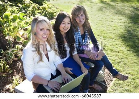 A group of Young, attractive female students outside studying - stock photo