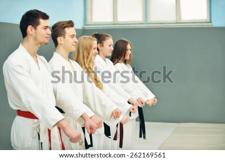a group of young, beautiful and successful karate women and men posing with karate master - stock photo