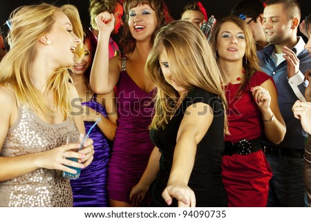 A group of young beautiful people dancing at a disco, smiling - stock photo