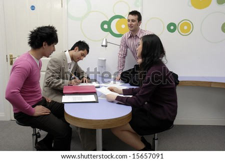 A group of young business entrepreneurs in a casual contemporary office space.