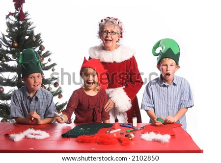 A group of young children aged 6 - 12 wearing elf hats and working with Mrs. Santa Claus on a Christmas craft project of decorating a stocking react with shock