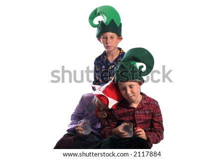 A group of young children in elf hats and pajamas drifting off to sleep after enjoying their milk and cookies