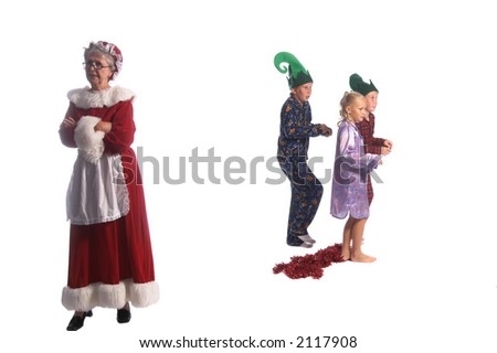 A group of young children  sneaking out of their rooms while Mrs. Santa Claus has her back turned to them