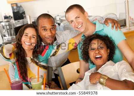 A group of young friends are laughing together while smiling at the camera.  Horizontal shot. - stock photo