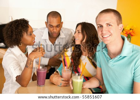 A group of young friends are socializing over smoothies.  One man is smiling at the camera.  Horizontal shot.