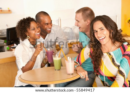 A group of young friends are socializing over smoothies.  One woman is smiling at the camera.  Horizontal shot. - stock photo