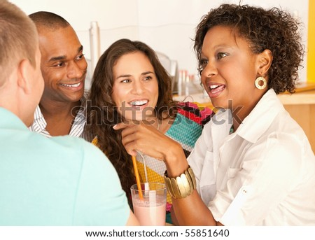 A group of young friends enjoy a conversation over smoothies.  Horizonal shot. - stock photo