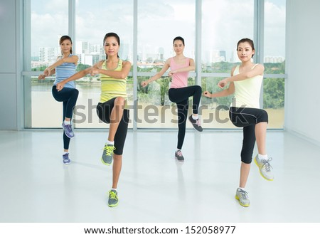 A group of young girls doing aerobics steps in the sport class