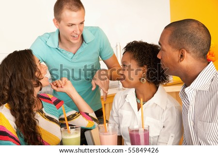A group of young people are socializing over smoothies.  Horizontal shot. - stock photo
