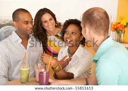 A group of young people are socializing over smoothies.  Horizontal shot.