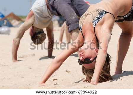 A group of young people to conduct classes in yoga in a warm summer day at the seashore