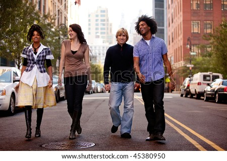 A group of young people walking down a street in a large city