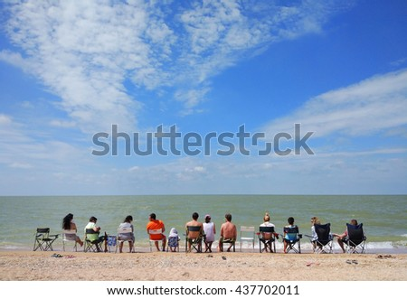 a group of young people with children is siting by the sea