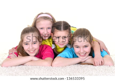 A group of young school girls in colorful T-shirts lying on the floor - stock photo