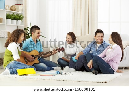 A group of young teenagers having fun in living room while one of them is playing a guitar - stock photo