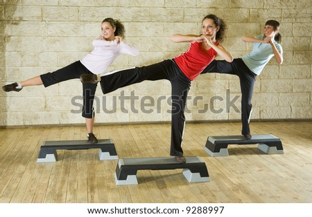 A group of young women exercising in the fitness club. Front view. - stock photo