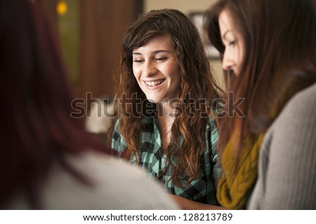 A group of young women sit together and smile. - stock photo