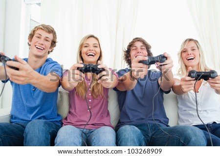 A group playing video games and smiling as they all look into the camera - stock photo