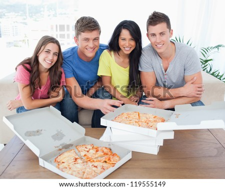A group sitting in front of delicious pizza as they look into the camera - stock photo