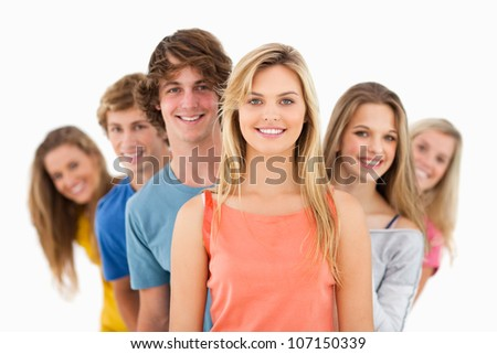 A group standing behind one another at varied angles looking at the camera - stock photo