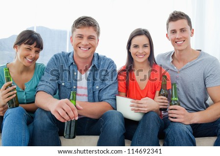 A group with beers in their hands as they sit on the couch together smiling
