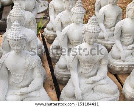 A grouping of cement buddha statues for sale at a garden center. - stock photo