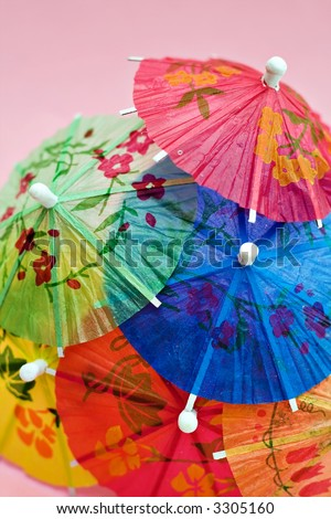 A grouping of colorful party drink umbrellas against a pink background. - stock photo