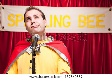 A grown man pretending to be a young boy competing in a spelling bee. - stock photo