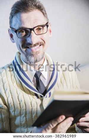 a grown man reading book sitting and smiles and looking at the viewer in the camera