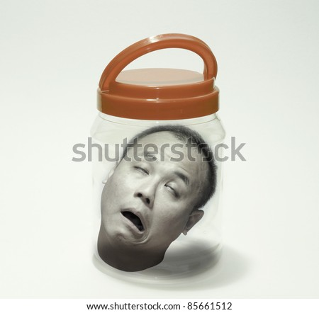 A gruesome image of a decapitated head of a man pickled in a jar for Halloween. - stock photo
